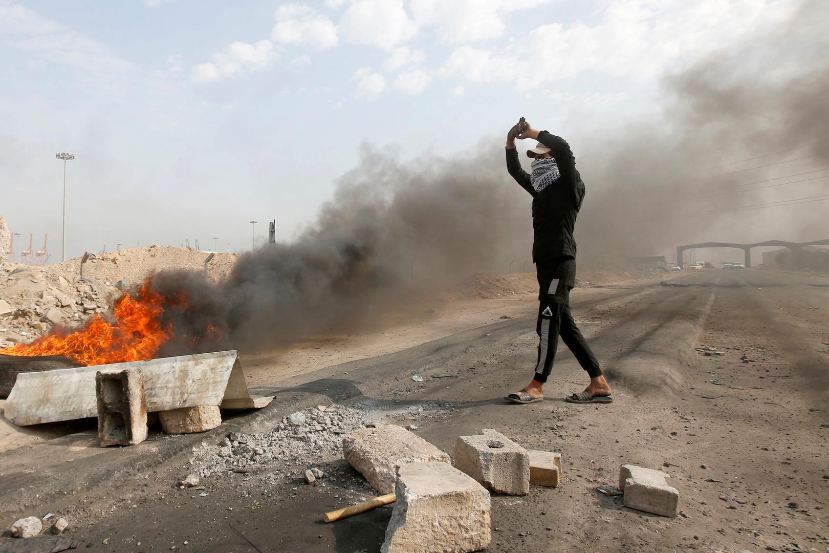 متظاهر عراقي يحرق إطارات لعرقلة الدخول إلى ميناء أم قصر