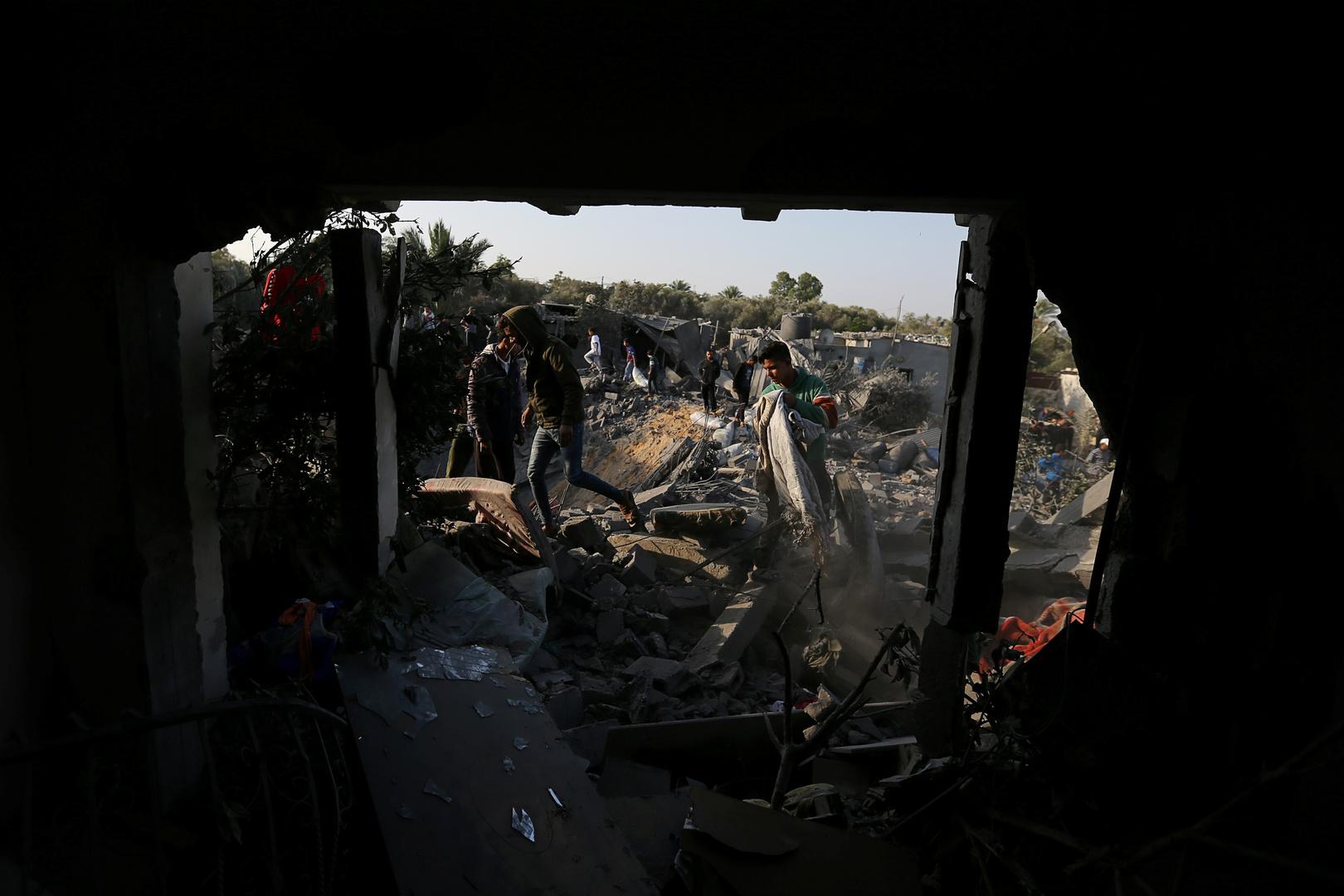 فلسطينيون يتفقدون منزلا تم تدميره بغارة جوية إسرائيلية في جنوب قطاع غزة