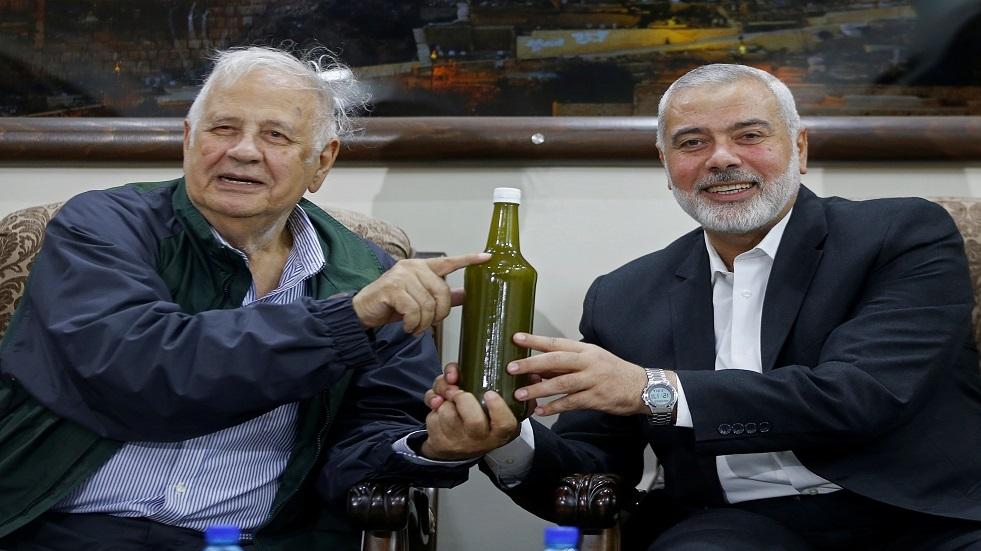 إسماعيل هنية وحنا ناصر يرفعان قنينة زيت زيتون فلسطيني بعد اجتماعهما في غزة - أرشيف