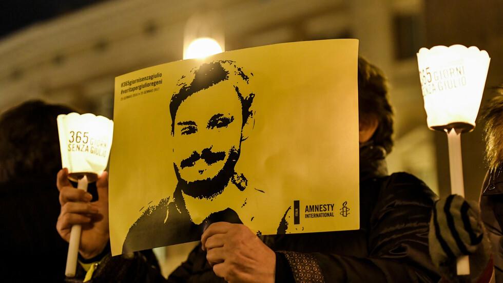 شخص يمسك صورة لجوليو ريجيني خلال وقفة جرت في روما يوم 25 يناير 2017 لإحياء ذكرى مقتله