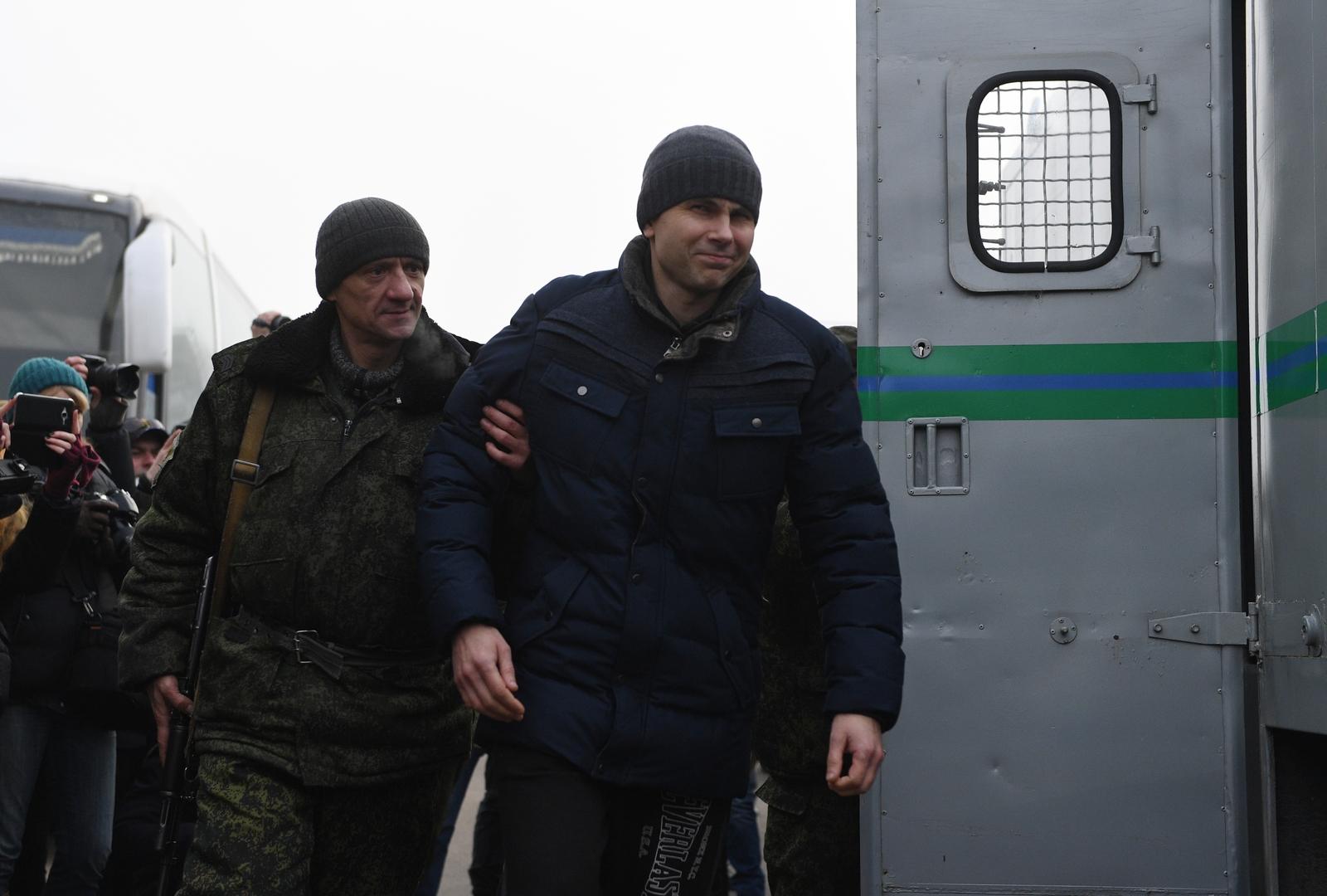 عنصر من قوات دونيتسك يرافق أسيرا من الجيش الأوكراني خلال تبادل الأسرى مع كييف