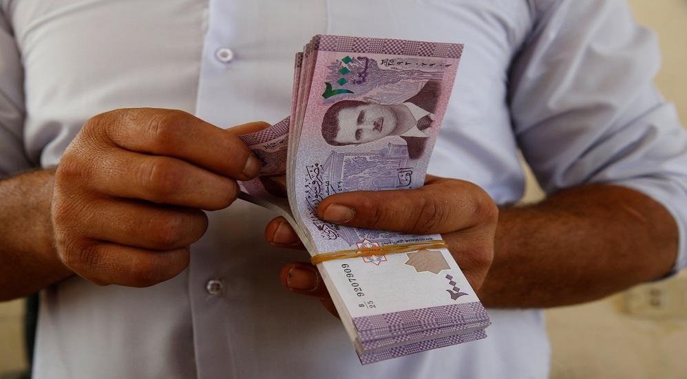 رجل يحصي أموالا بالعملة السورية