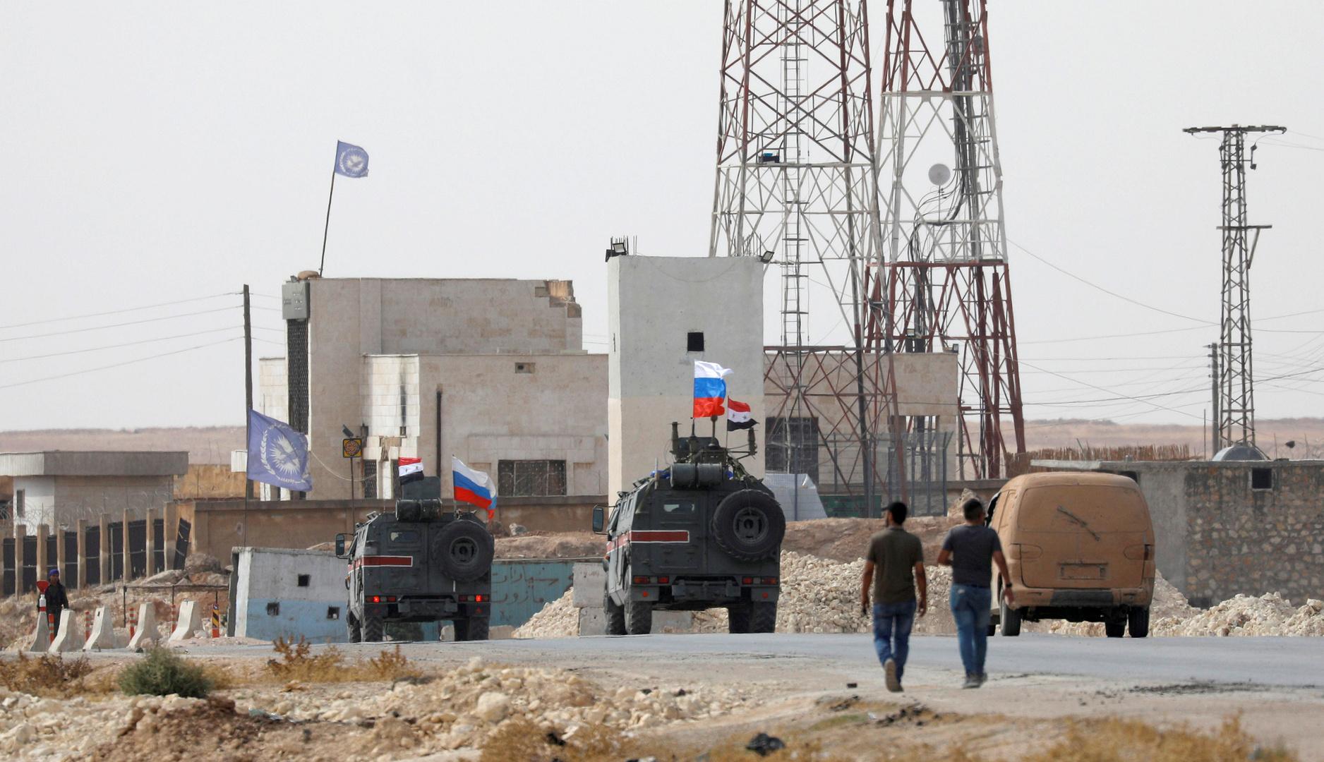 عربتان عسكريتان عليهما علما روسيا وسوريا قرب مدينة منبج