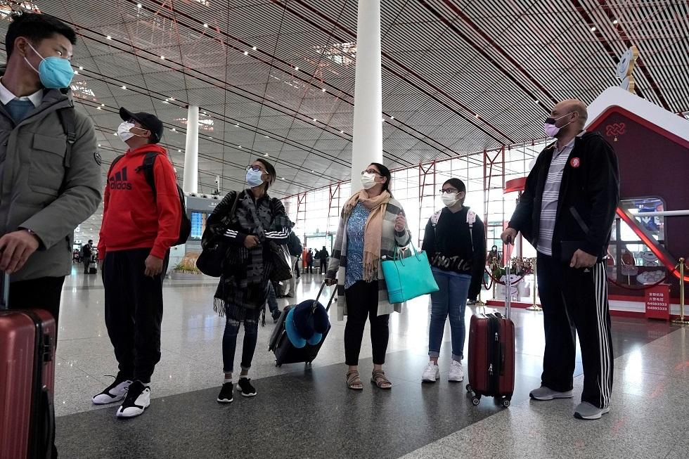 مسافرون يضعون أقنعة للوقاية من انتقال عدوى كورونا