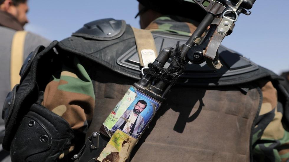 أحد أنصار الحوثيين يحمل رشاشة وعليها صورة زعيم الجماعة