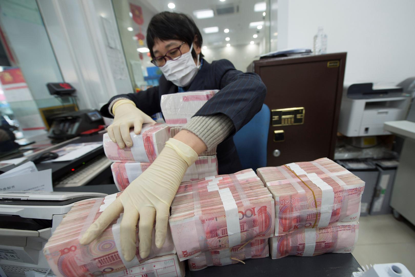 موظف يرتدي قناعًا للوجه يرتب أكوام الأوراق النقدية لليوان الصيني في أحد البنوك في نانتونغ