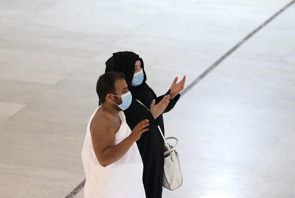 معتمران يضعان كمامتين للوقاية من كورونا في مكة المكرمة