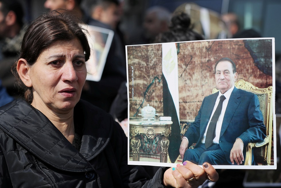 مؤيدة لمبارك تحمل صورته أثناء مراسم دفنه