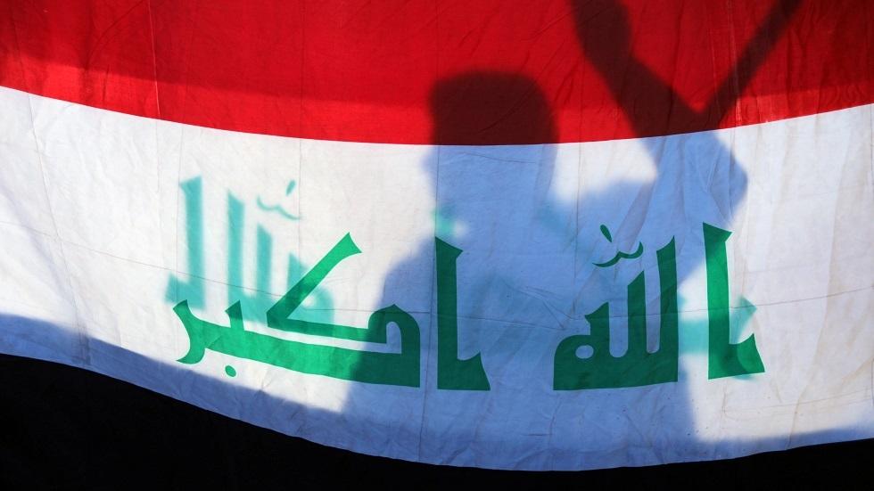 متظاهر يقف خلف العلم العراقي - أرشيف