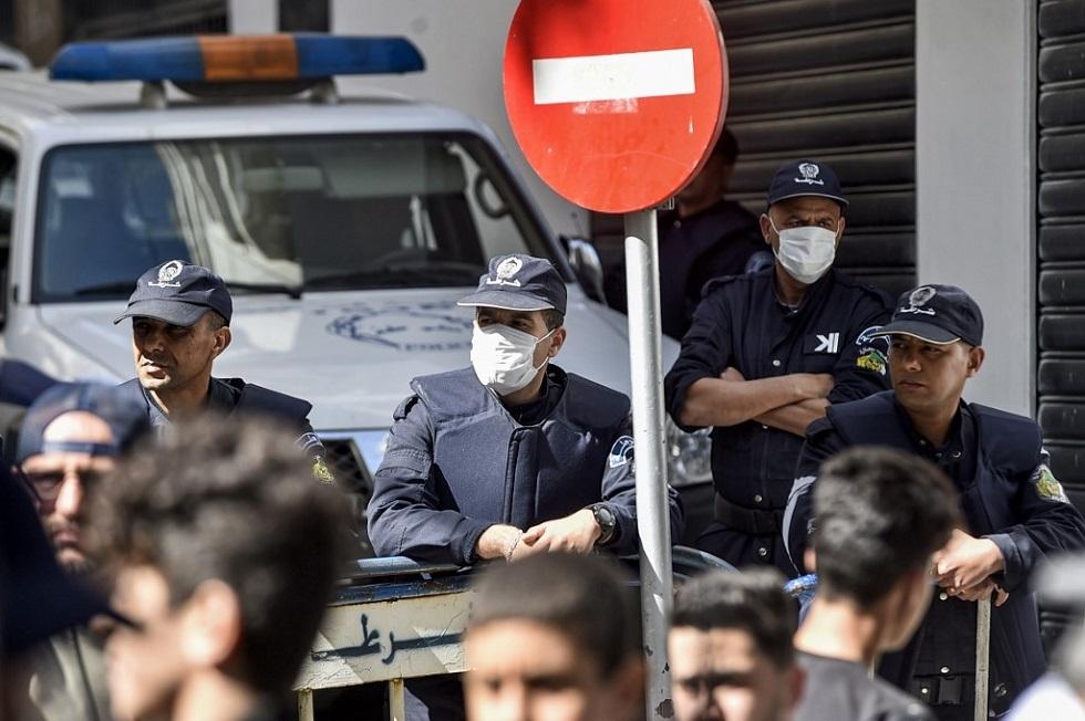 رجال شرطة يرتدون كمامات واقية في الجزائر