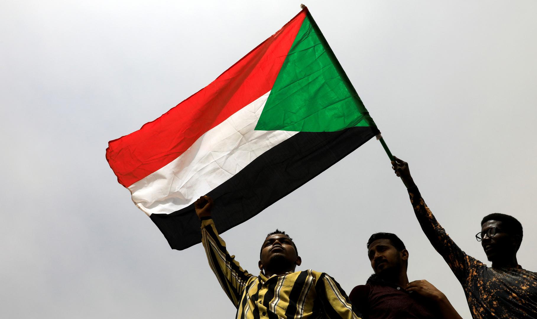مواطنون سودانيون في الخرطوم يحملون علم بلادهم
