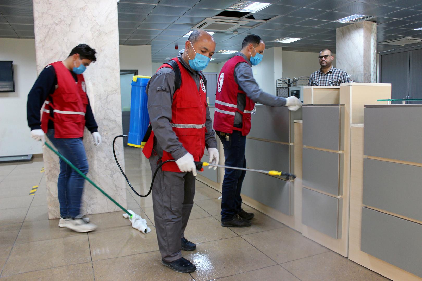 أفراد من الهلال الأحمر يعقمون الأماكن العامة في مدينة مصراتة الليبية