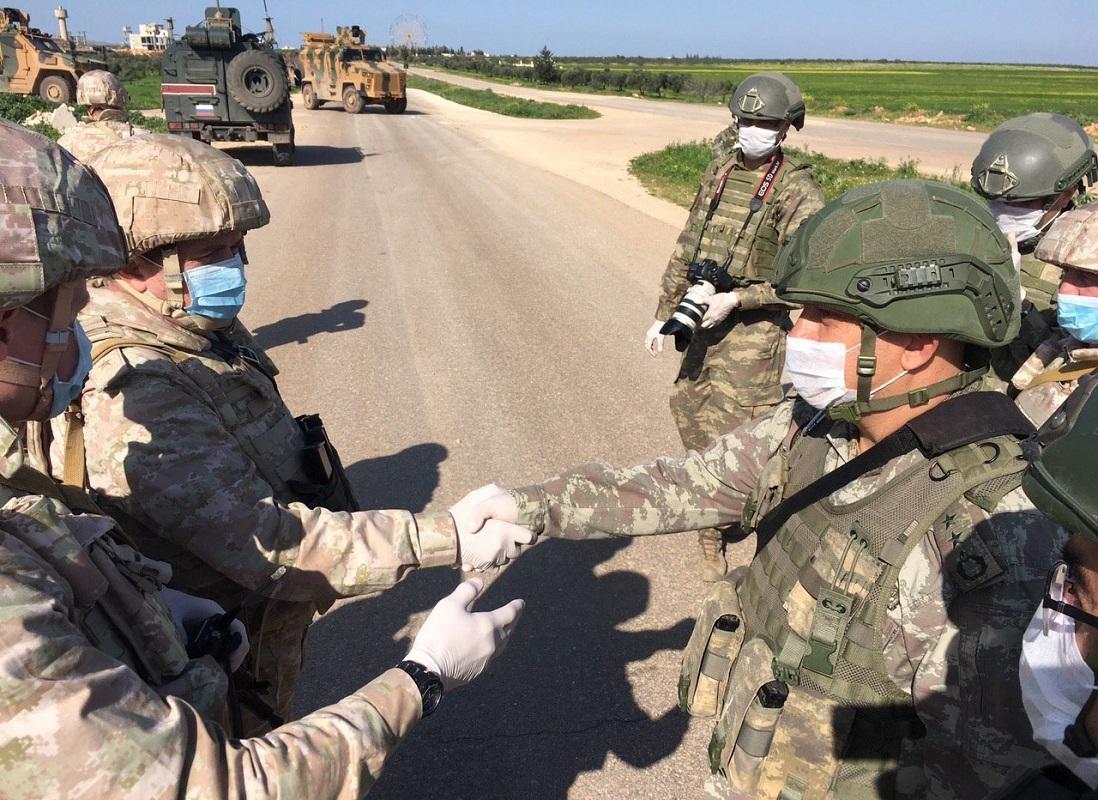 عسكريون روس وأتراك أثناء تسيير دورية مشتركة بين البلدين على طريق M4 الاستراتيجي في محافة إدلب السورية