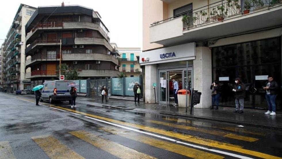 يصطف المتسوقون تحت المطر في صقلية بمسافات متباعدة في ظروف الحجر الصحي