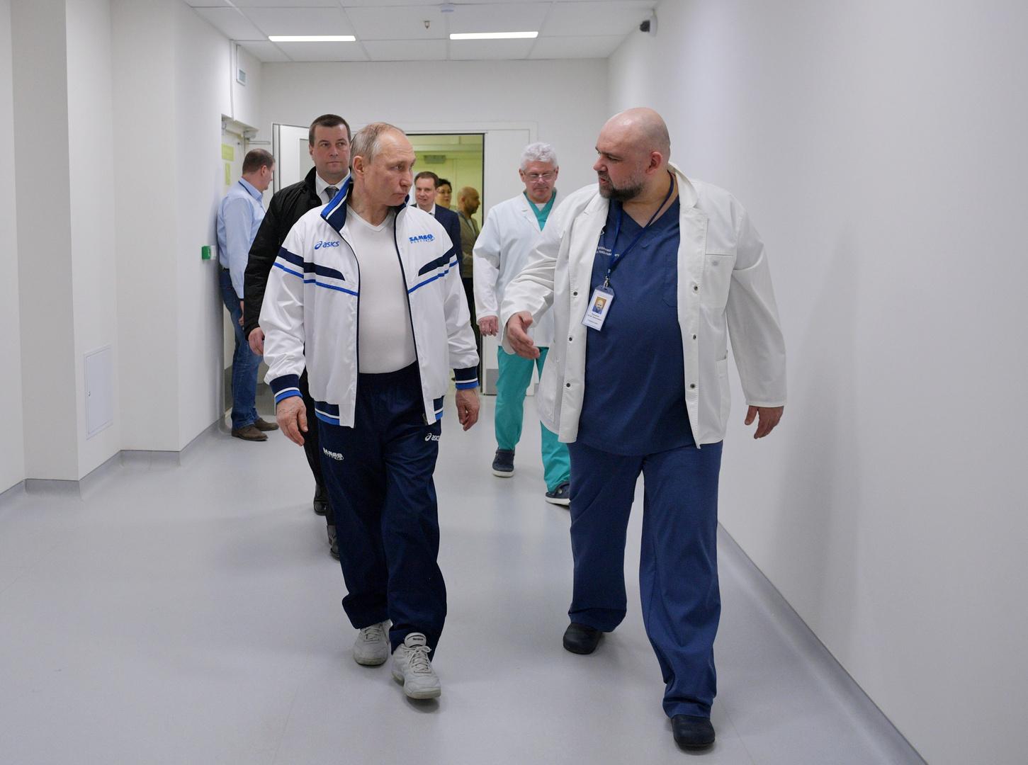 الطبيب دينيس بروتسينكو يرافق الرئيس فلاديمير بوتين أثناء زيارة الأخير إلى المستشفى المخصص لمعالجة المصابين بفيروس كورونا في بلدة كوموناركا بضواحي موسكو - 24 مارس 2020