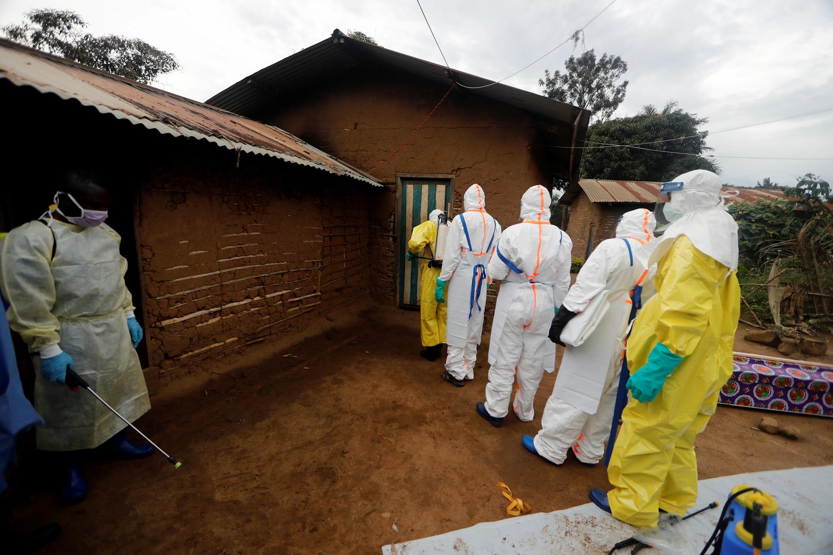 موظفون طبيون في مدينة بني شرق جمهورية كونغو الديمقراطية يتفقدون منزلا توفيت فيه سيدة مصابة بفيروس