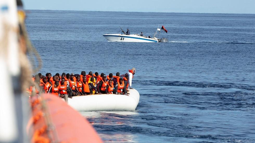 قارب دورية لخفر السواحل الليبي قرب زورق مهاجرين في البحر المتوسط - أرشيف