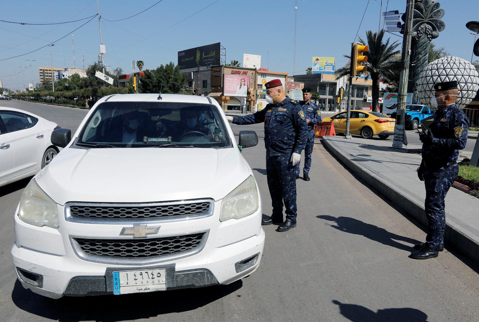 ضابط شرطة يراقب سيارة في بغداد