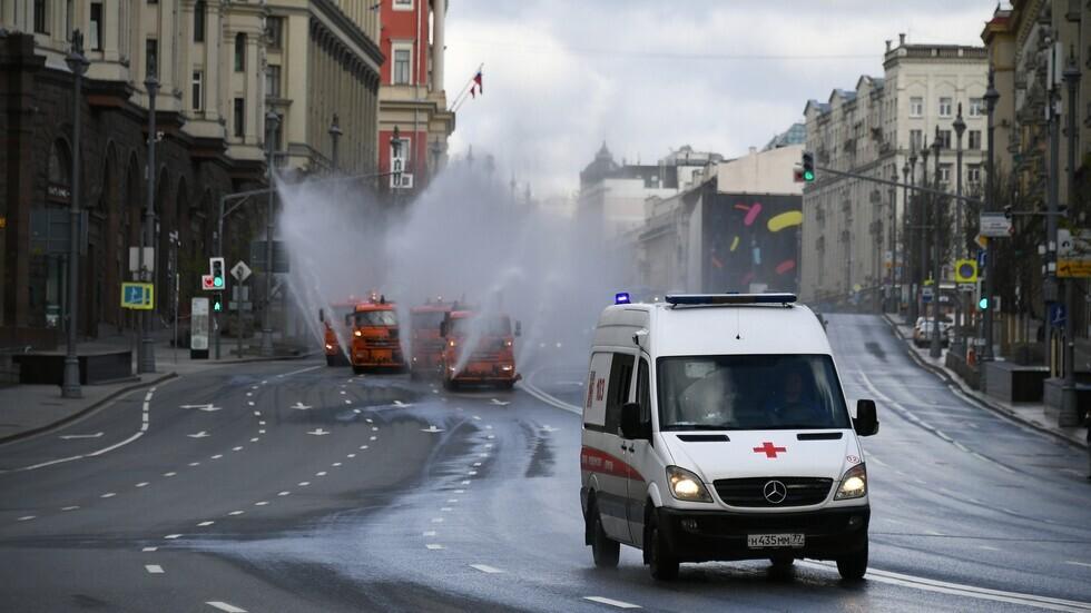 سيارة إسعاف وسط موسكو على خلفية عربات تطهير صحي.