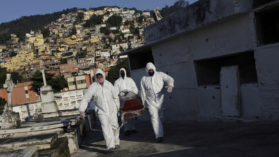 موظفو مكتب جنازة برازيلي ينقلون تابوتا لشخص توفي بفيروس كورونا في مدينة ريو دي جانيرو.