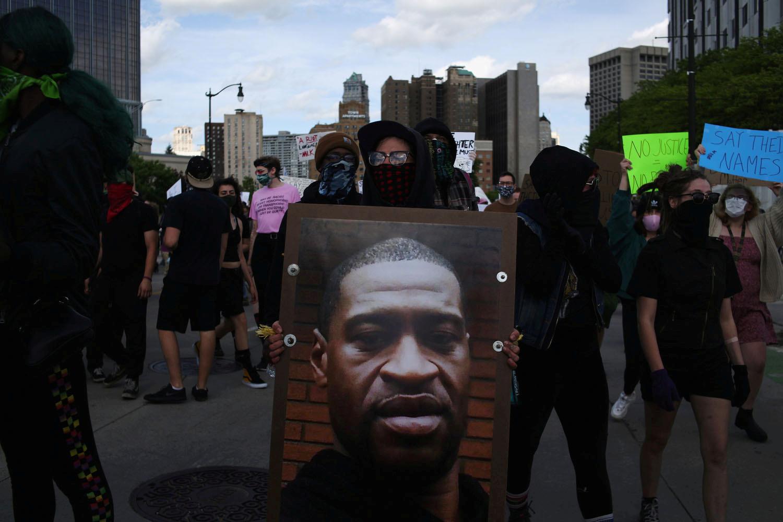 متظاهرة مشاركة في احتجاج ضد العنصرية في مدينة ديترويت تحمل صورة للمواطن الأمريكي من أصول إفريقية، جورج فلويد، الذي قتل جراء عملية القبض عليه من قبل عناصر شرطة في مينيابوليس يوم 25 مايو.