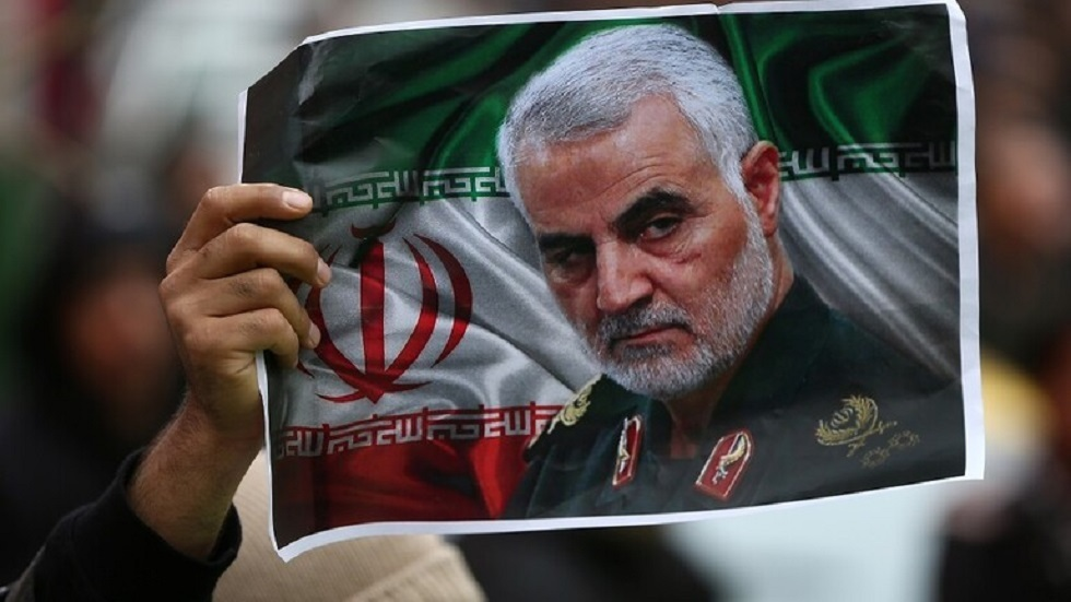 مواطن إيراني يحمل صورة سليماني اثناء تشييعه