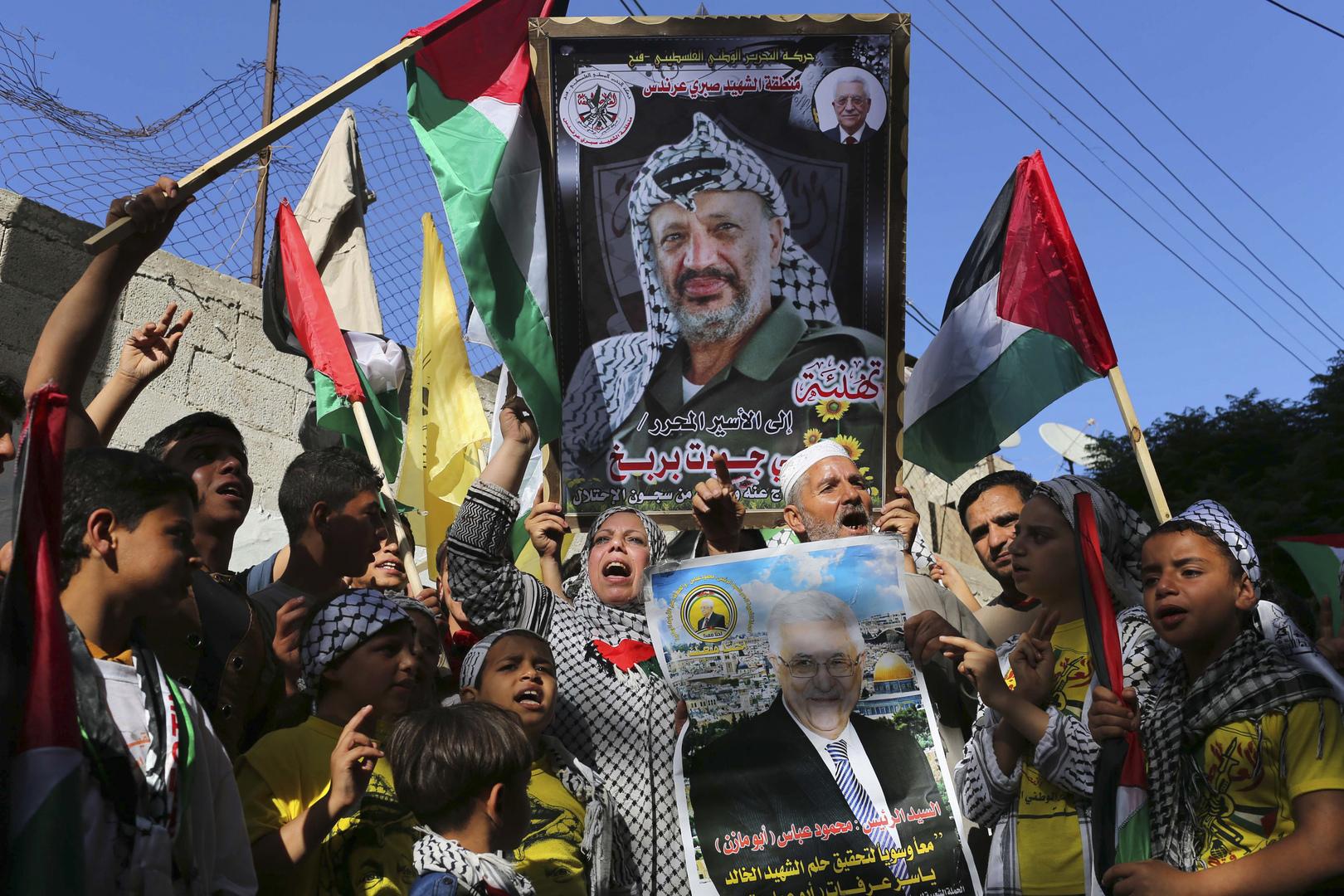 متظاهرون فلسطينيون يحملون صورة للزعيم الفلسطيني الراحل ياسر عرفات