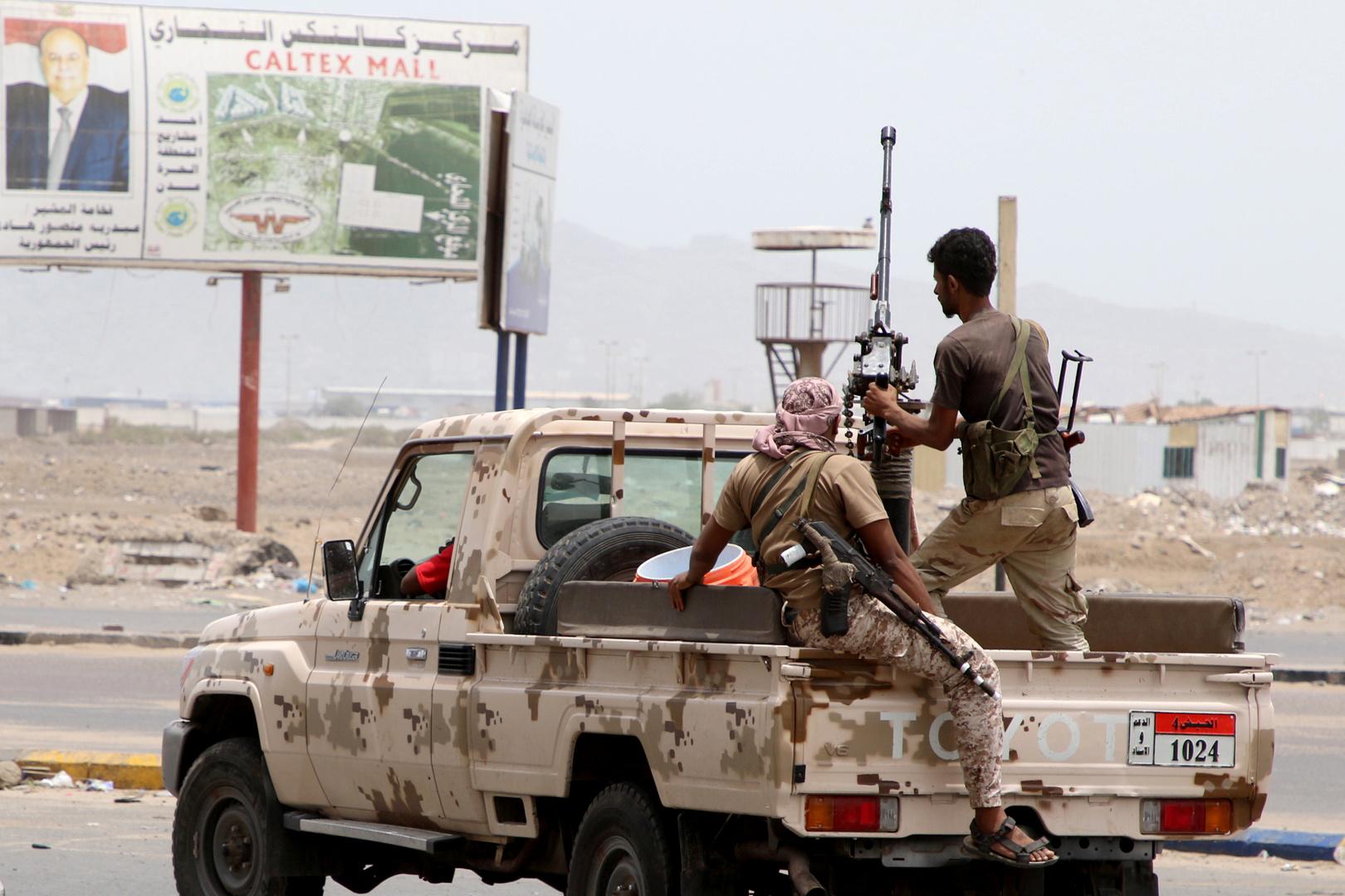 عناصر للمجلس الانتقالي الجنوبي على خلفية لافتة مع صورة الرئيس اليمني عبد ربه منصور هادي - عدن