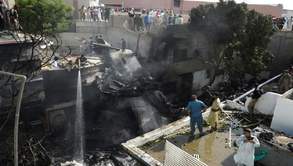 رجال الإطفاء يرشون المياه على حطام طائرة الخطوط الجوية الدولية الباكستانية بعد تحطمها في كراتشي يوم 22 مايو