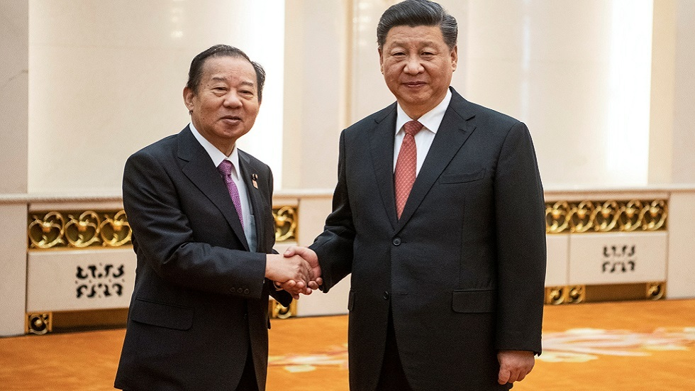 الرئيس الصيني شي جين بينغ يصافح الأمين العام للحزب الديمقراطي الليبرالي الحاكم الياباني توشيهيرو نيكاي أثناء زيارته إلى بكين في أبريل 2019