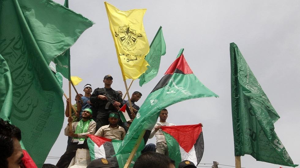 """فلسطينيون يلوحون بأعلام """"فتح"""" و""""حماس"""" في غزة (صورة أرشيفية)"""