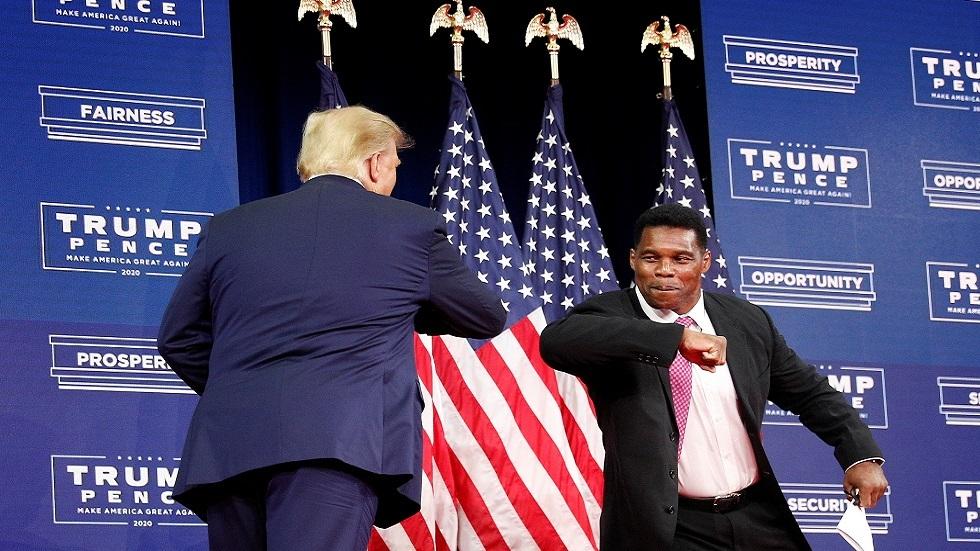 الرئيس الأمريكي دونالد ترامب يتبادل التحية مع لاعب كرة القدم المتقاعد هيرشل ووكر قبل اجتماع في أتلانتا