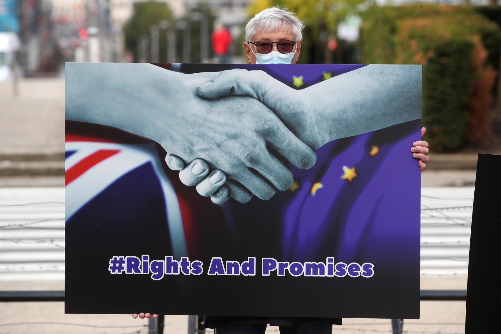 رجل يحمل صورة لمصافحة بين بريطانيا والاتحاد الأوروبي