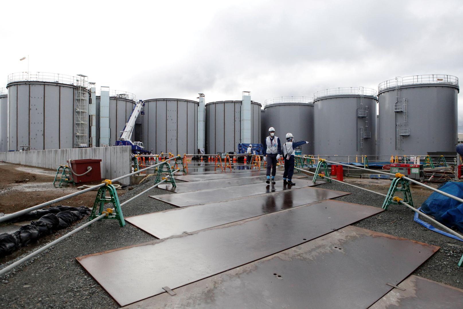 عمال يقفون بالقرب من صهاريج تخزين للمياه المشعة في محطة فوكوشيما دايتشي للطاقة النووية