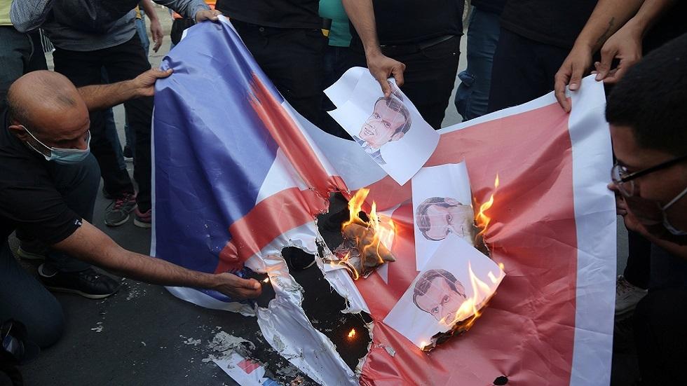 محتجون يحرقون العلم الفرنسي وصورا للرئيس إيمانويل ماكرون أمام مقر السفارة الفرنسية في بغداد