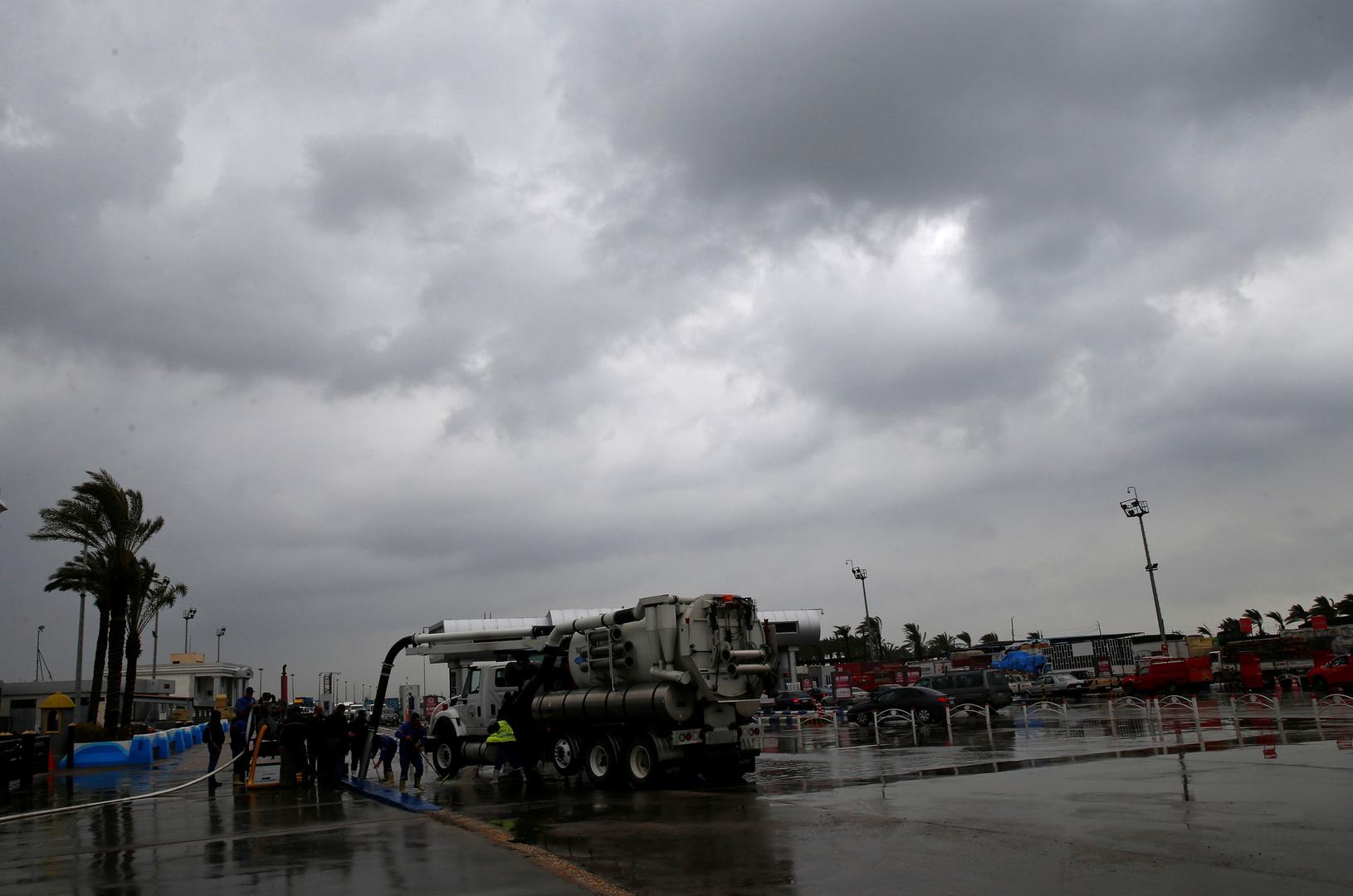 عمال يزيلون المياه بعد هطول أمطار غزيرة بسبب سوء الأحوال الجوية في مدينة الإسكندرية بمصر