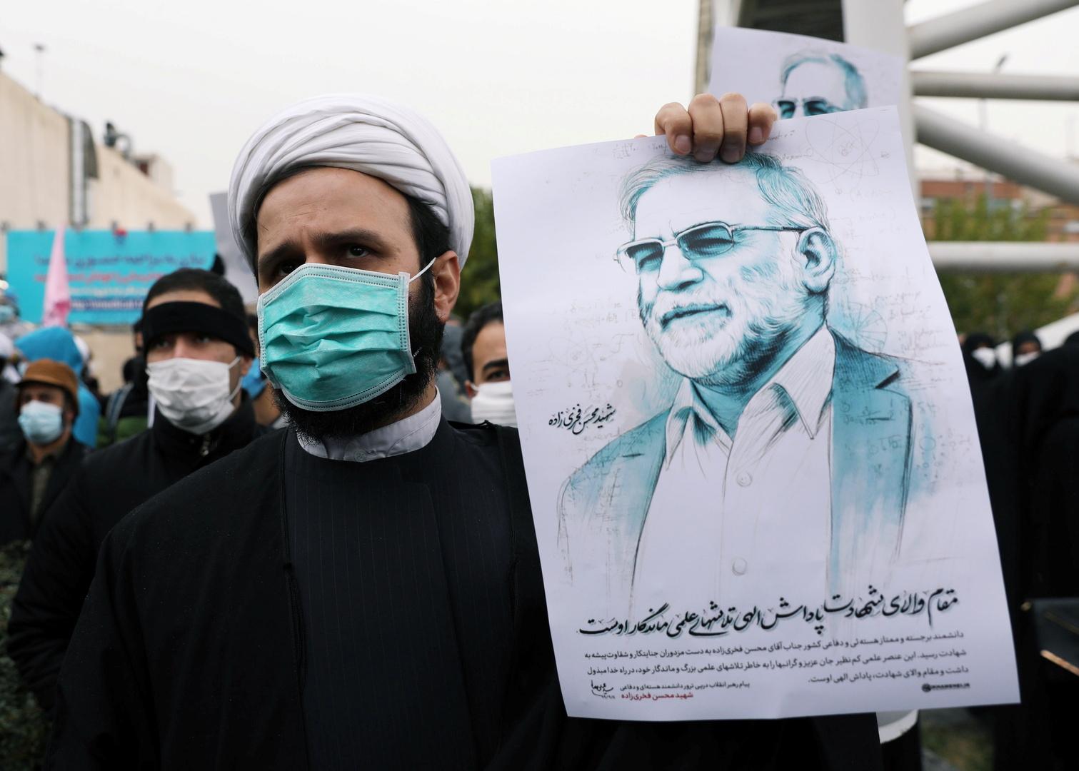 شيخ إيراني يحمل صورة العالم الإيراني محسن زادة