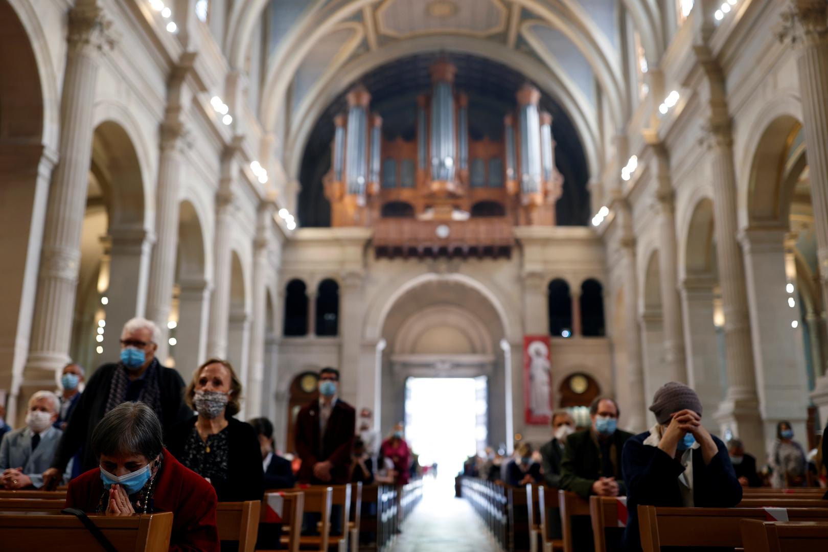 مصلون يحضرون قداسا في كنيسة ويرتدون كمامات في ظل انتشار فيروس كورونا بفرنسا