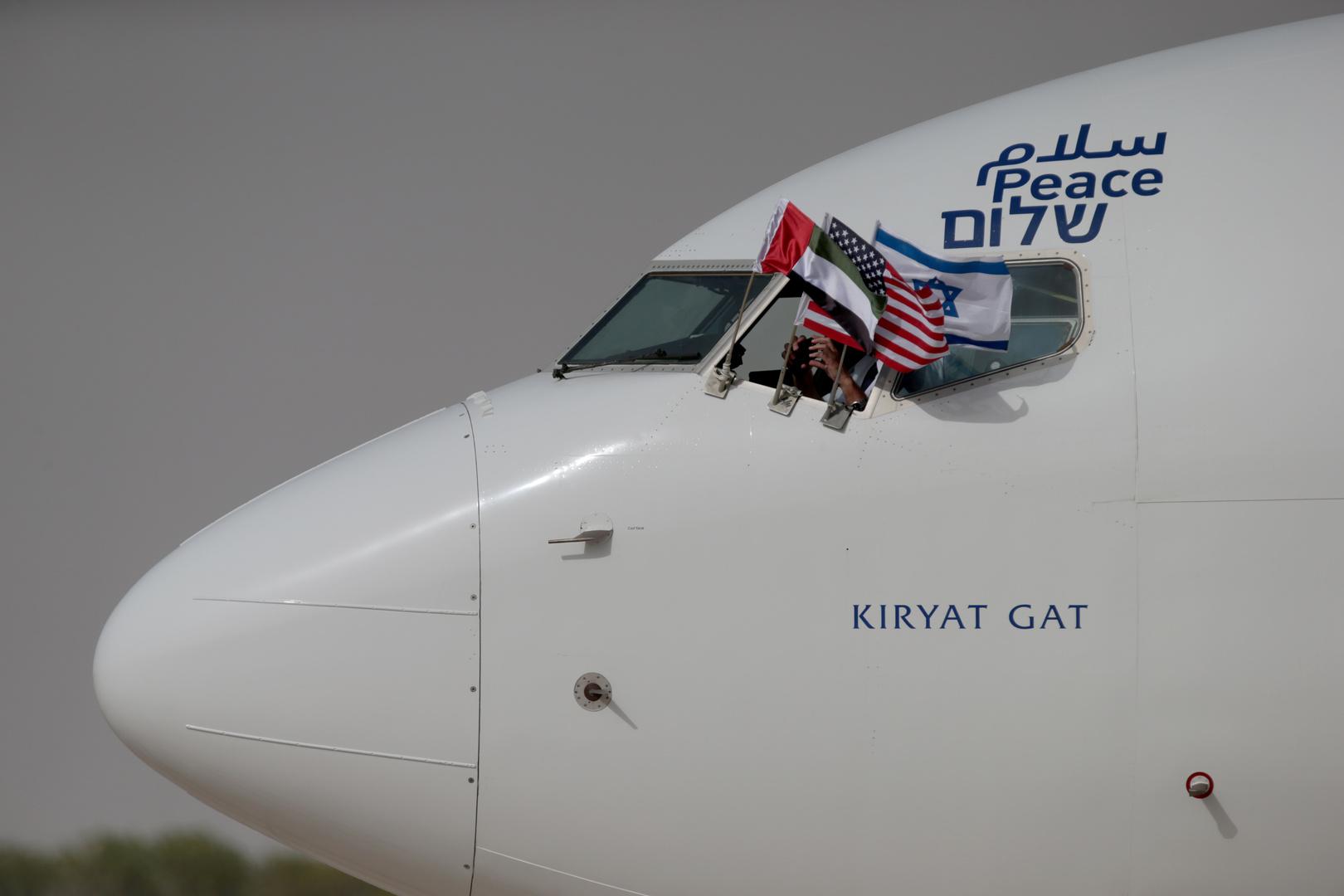 العلم الإماراتي والعلم الإسرائيلي والعلم الأمريكي على نافذة طائرة إسرائيلية مكتوب عليها