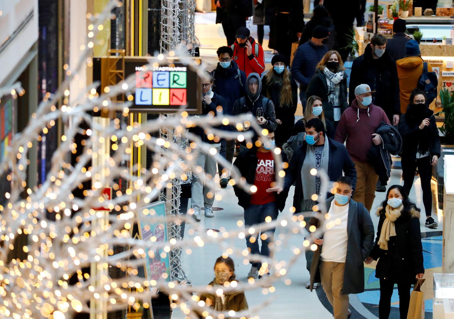 مواطنون ألمان يرتدون كمامات أثناء سيرهم بجانب زينة عيد الميلاد في العاصمة برلين في ظل تفشي فيروس كورونا