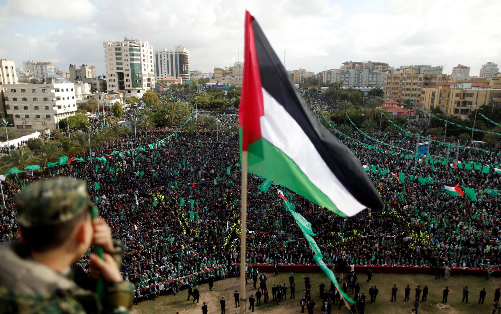العلم الفلسطيني فوق أنصار  حركة حماس في مسيرة بمناسبة الذكرى الثلاثين لتأسيس الحركة، في قطاع غزة بفلسطين