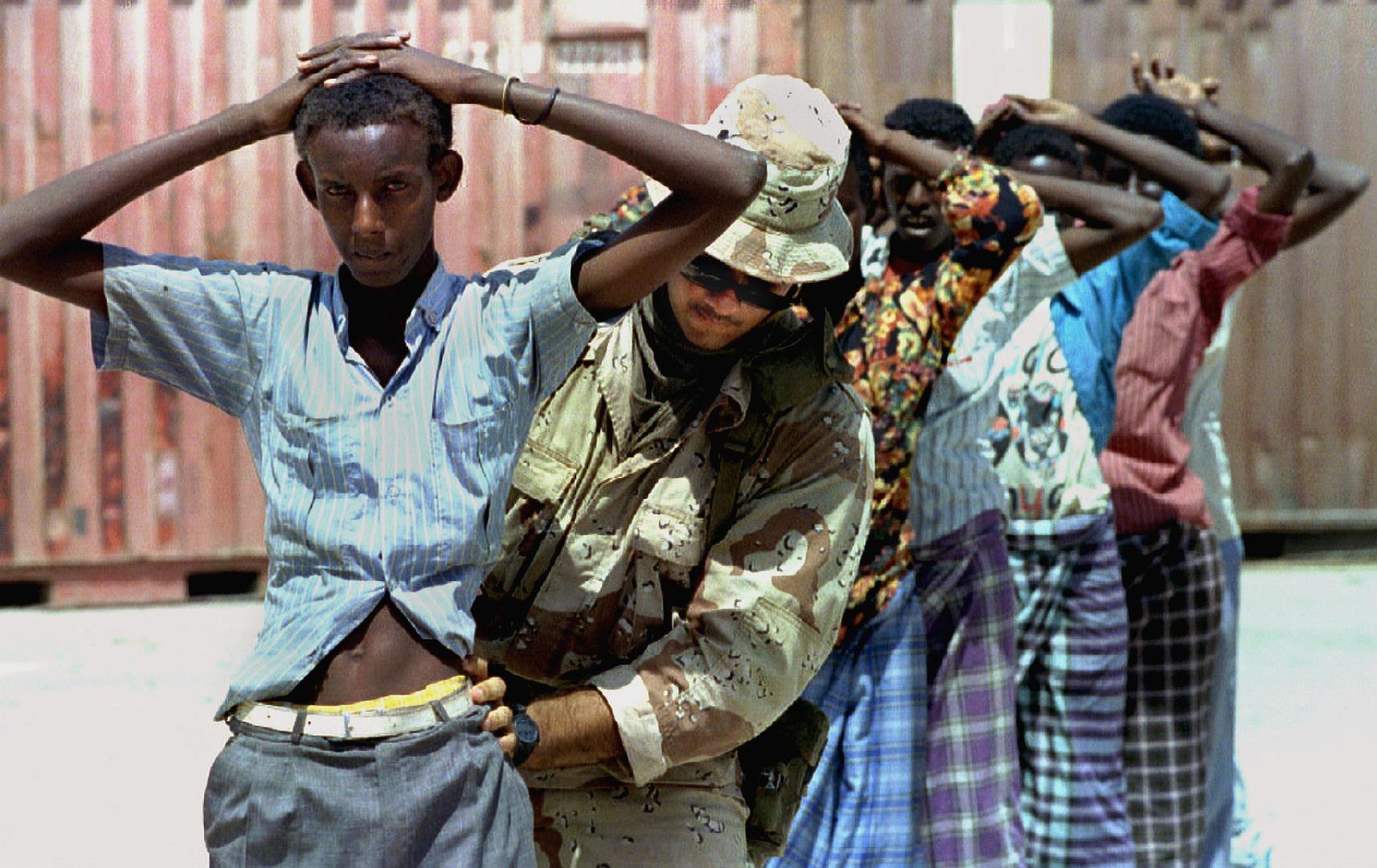 جندي أمريك يفتش صوماليين وسط العاصمة الصومالية مقديشو سنة 1992.