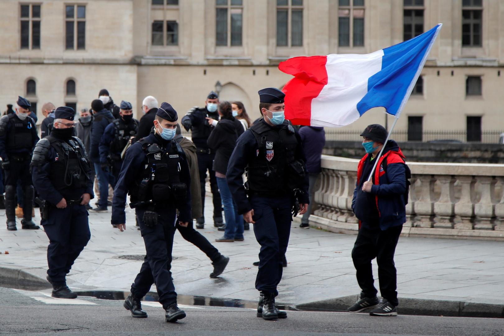شخص يحمل العلم الفرنسي وبجانيه رجال شرطة في بارس