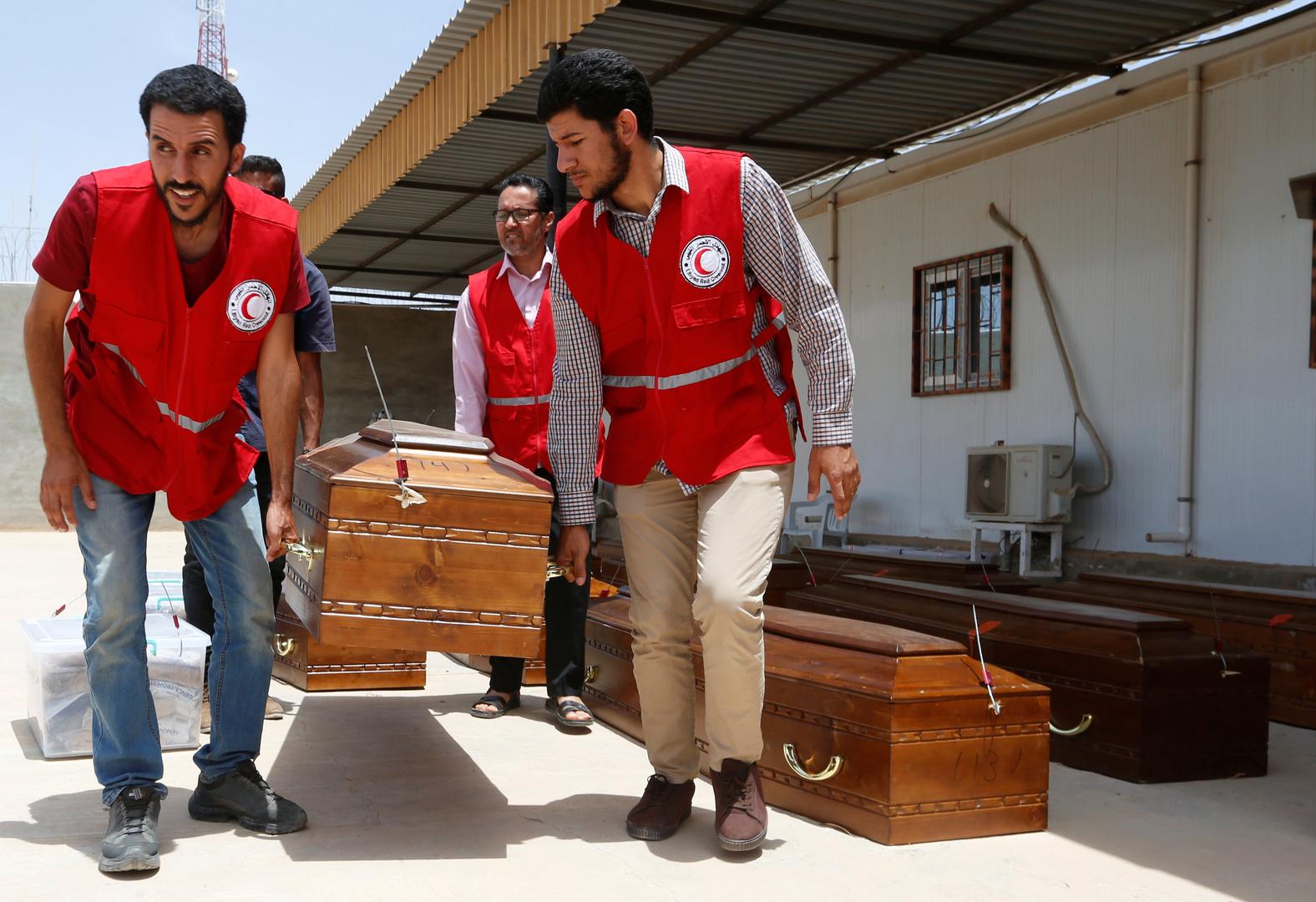 عناصر من الهلال الأحمر الليبي يحملون نعش
