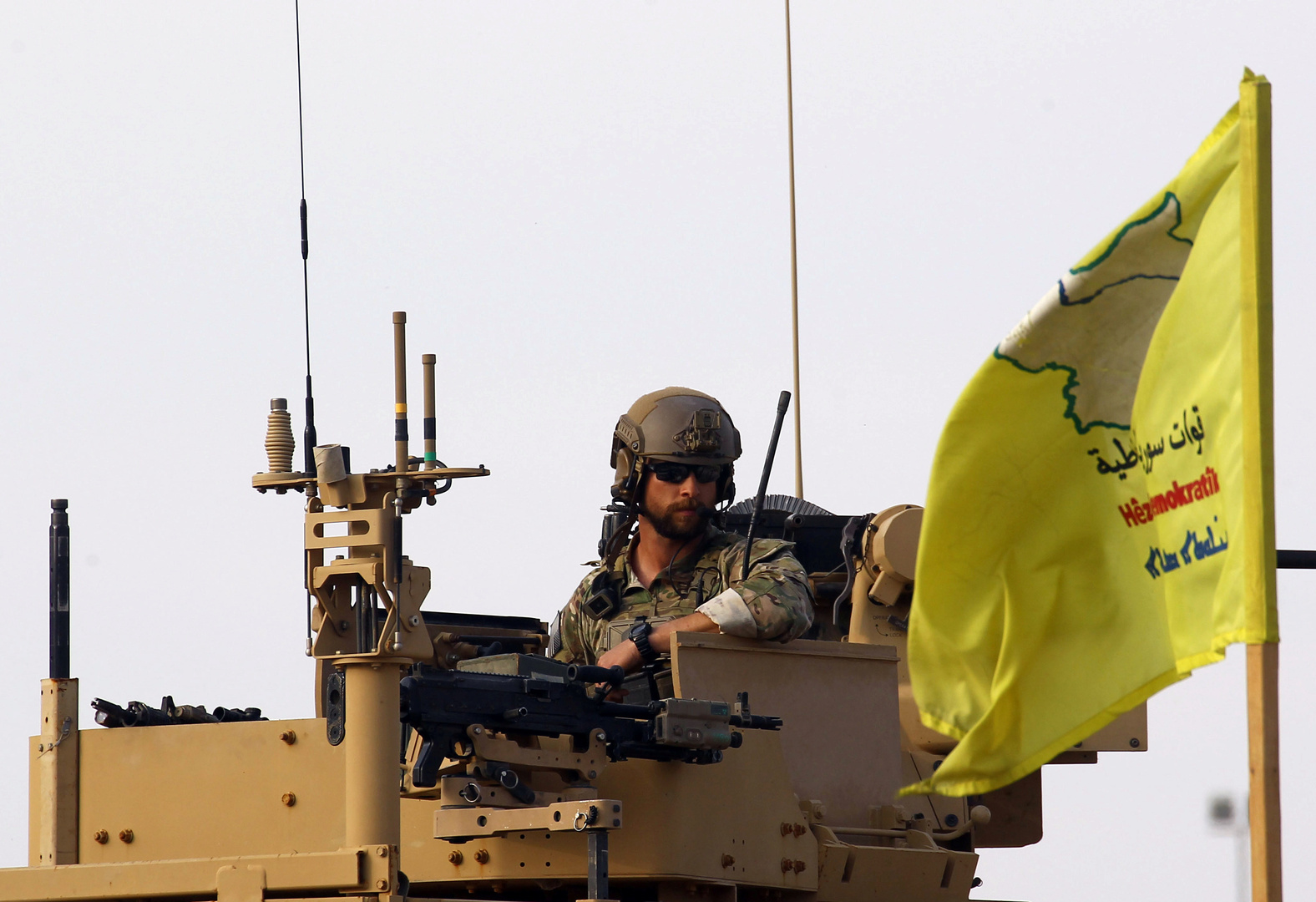 عسكري أمريكي أمام علم الإدارة الذاتية في شمال وشرق سوريا في حقل النفط العمل بمحافظة دير الزور.