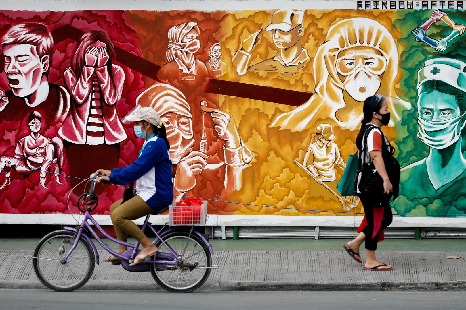 فلبينيات يضعن الكمامات في العاصمة مانيلا