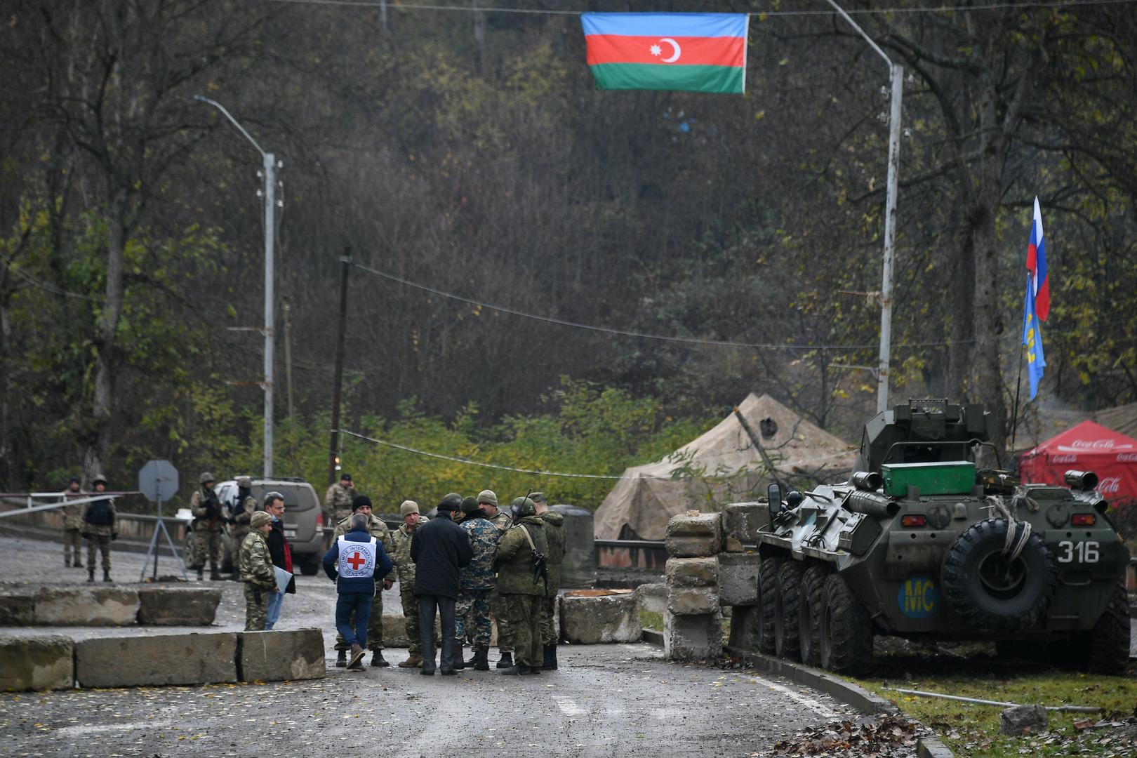 عناصر من القوات الأذربيجانية وقوات حفظ السلام الروسية وموظفون من الصليب الأحمر في نقطة تفتيش على الطريق بين شوشا وستيباناكيرت في إقليم قره باغ.