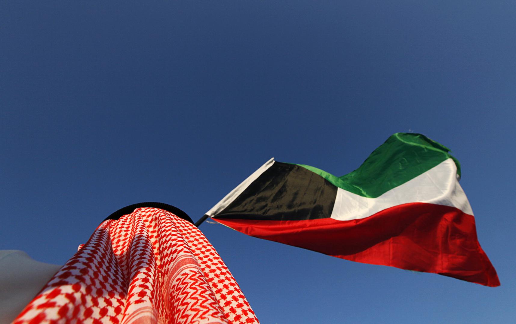 رجل يحمل العلم الكويتي