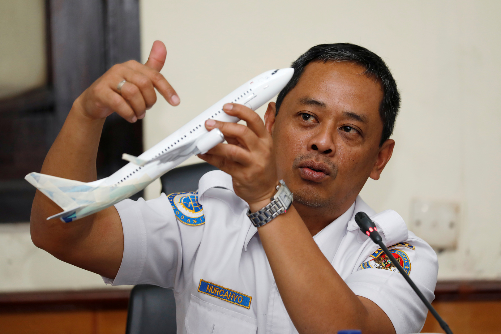 رئيس لجنة حوادث الطيران في إندونيسيا يحمل نموذج طائرة، صورة تعبيرية