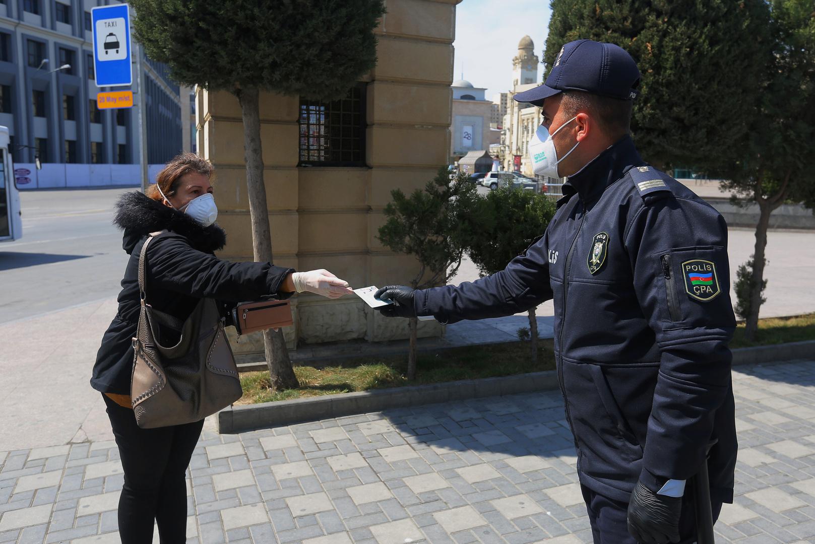 شرطي يتأكد من إذن الخروج لمواطنة في أذربيجان ضمن الإجراءات الصحية في مواجهة فيروس كورونا
